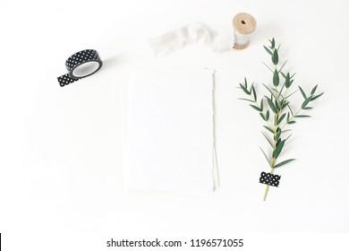 Feminine stationery, wedding desktop mock-up scene. Blank greeting card, envelope,black washi tape, silk ribbon and green Eucalyptus parvifolia branch.White table background. Flat lay, top view.