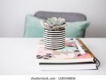 A feminine styled stock office photo with peach and teal colors, a white desk, teal pillow and succulent.