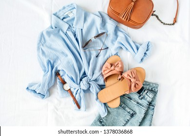 Feminine summer fashion composition with blouse, slippers, purse, sunglasses, watch, jean shorts on white background. Flat lay, top view minimalist clothes collage. Female fashion blog, social media.
