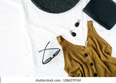 Feminine summer fashion composition with hat, blouse, earrings, purse, sunglasses on white background. Flat lay, top view minimalist clothes collage. Female fashion blog, social media, website hero.