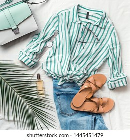 Feminine summer fashion composition: striped blouse, slippers, bag, sunglasses, watch, perfume, jeans, palm leaf on white background. Flat lay, top view clothes. Female fashion blog or social media