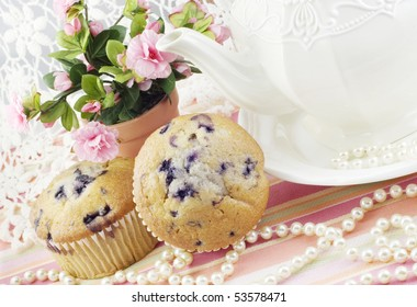A feminine tea party with fresh blueberry muffins, roses, lace and pearls
