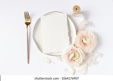 Feminine wedding, birthday desktop mock-up scene. Porcelain plate, blank craft paper card, silk ribbon, blush pink Persian buttercup flowers and fork. White table background. Flat lay, top view.
