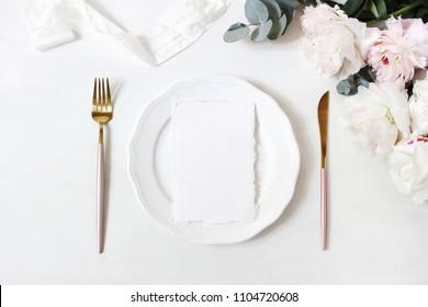 Feminine wedding, birthday desktop mock-up scene. Porcelain plate, blank craft paper greeting cards, silk ribbon, golden cutlery, eucalyptus, peony flowers. White table background. Flat lay, top view