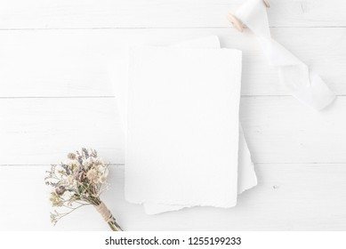 Feminine wedding, birthday desktop mock-up. Invitation card mockup, template Blank greeting cards, rspv card, 5x7, card, envelope. White silk ribbons, dry flowers. White wooden background. Flat lay