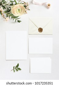 Feminine wedding, birthday desktop mock-ups. Blank greeting cards, envelope. Eucalyptus branches, pink cherry tree blossoms and Persian buttercup flowers. White table background. Flat lay, top  view.