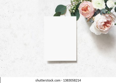 Feminine wedding, birthday mock-up scene. Blank paper greeting card. Bouquet of blush pink English roses, ranunculus flowers and eucalyptus leaves. Concrete table background. Flat lay, top view.