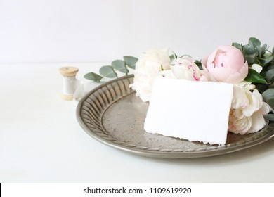 Feminine wedding or birthday table composition with floral bouquet. White and pink peonies flowers and eucalyptus branches  on old vintage silver tray, craft paper card and silk ribbon.
