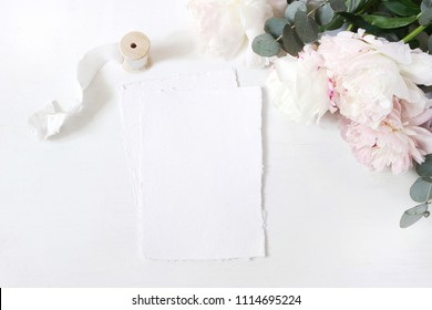 Feminine wedding or birthday table composition with floral bouquet. White and pink peonies flowers, eucalyptus and silk ribbon. Blank cotton paper cards mockups, invitations. Flat lay, top view.