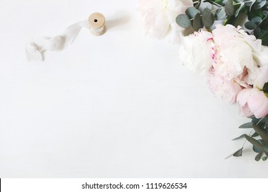 Feminine wedding or birthday table composition with floral bouquet. White and pink peonies flowers, eucalyptus and silk ribbon. Festive greeting card, invitation. Empty space. Flat lay, top view.