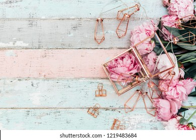Feminine wedding or birthday table composition with pink peonies and gold decorations on old vintage wooden table.top view, copy space