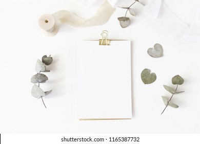 Feminine wedding desktop stationery mockup with blank greeting card, dry eucalyptus leaves, silk ribbon and golden binder clip on white table background. Flat lay, top view.