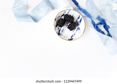 Feminine wedding or summer table composition. Porcelain plate with blackberry fruit and blue silk ribbons. Empty space. Flat lay, top view.