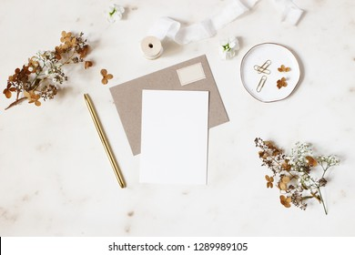 Feminine winter wedding, birthday stationery mock-ups scene. Blank greeting card, kraft envelope, golden pen, dry hydrangea and gypsophila flowers. Marble stone table background. Flat lay, top view.