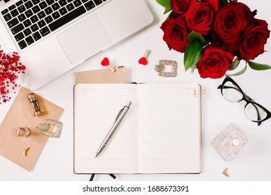Feminine work space of office worker with beautiful bouquet of red roses and opened notebook on white background. Mood and blogging concept.
