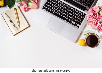 Feminine workspace border with keyboard, coffee and flowers, top view and copy space