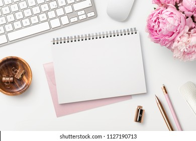 feminine workspace / desk with blank open notepad, keyboard, stylish office / writing supplies and pink peonies on a white background, top view