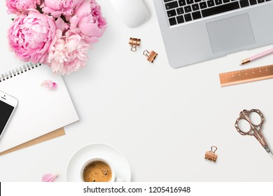 feminine workspace with laptop computer, smartphone, office supplies, a bunch of peonies and coffee on a white desk, top view / flat lay, copyspace for your text or headline