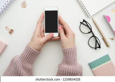 Feminine workspace mockup with smartphone in female hands, notebook, spectacles, notepad, pen and office supplies. Flat lay, top view