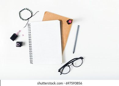 Feminine workspace with notepad, pencil, lipstick, spectacles, bracelet and nail polish on white background. Flat lay, top view office desk