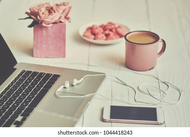 Feminine workspace - worksplace with keyboard, coffee and flowers. Bouquet of roses, cup of coffee and laptop on old wooden table. Creative planning concept. Top view. Toned image. Vintage style.