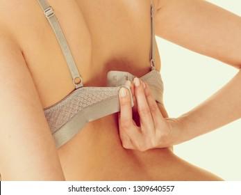 Femininity, brafitting, underwear, underclothes concept. Attractive slim woman take her grey bra off. Studio shot on bright background