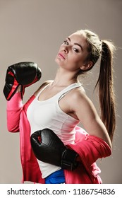Feminist and emancipation idea. Woman in male occupation, training, boxing. Fit female fitness girl doing exercise on grey background.