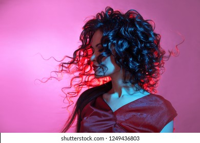 Femme fatale dancing, portrait in Studio with bright toning, blue and red color. Young attractive brunette, young woman in red dress