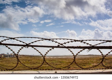 fence with barbed wire and an airport runaway with a partially clouded sky