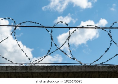 fence with barbwire against blue sky. Border or prison concept