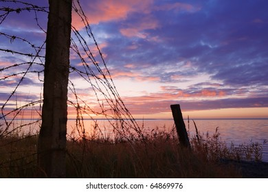 Fence, before a closely guarded, a naval base on the background of dawn.
