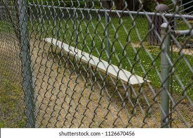fence and bench at baseball field at park
