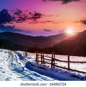 fence by the road to forest in the mountains on a fine winter sunset
