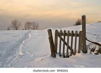 Fence, field ans snow : typical snowy lanscape in french jura, at dusk