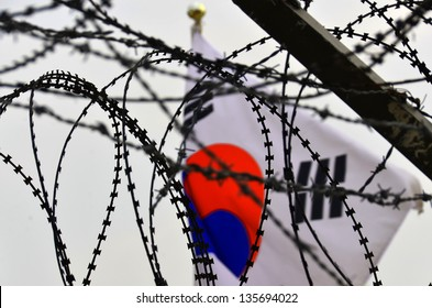 Fence and flag at the Korean Demilitarized Zone is a strip of land running across the Korean Peninsula that serves as a buffer zone between North & South Korea which runs along the 38th parallel north