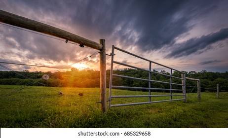 Fence and gate surrounding a country meadow at sunrise