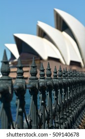 A fence line leads towards defocused Sydney Opera House background in Sydney, New South Wales, Australia.