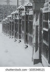 Fence made of cast iron lattices and granite columns in cloudy snowy weather.