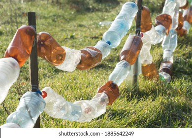 A fence made from old plastic bottles. Recycling and processing of inorganic waste.