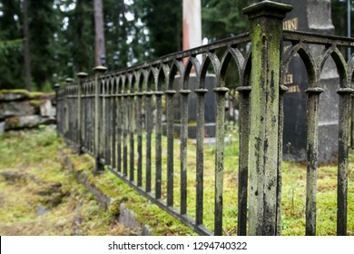 Fence at old semetery in Finland with grave crosses and stones
