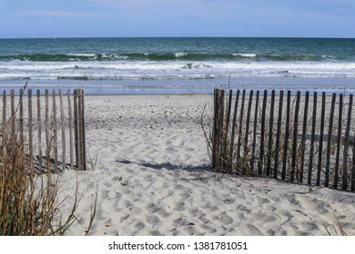 Fence on beach leading to ocean in Myrtle Beach, South Carolina.