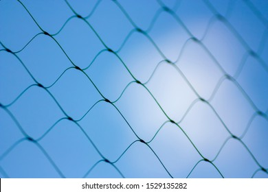 Fence on a blue sky with cloud, Mesh fence with partly cloudy sky, Chain link fence and a blue sky, fence and Blue sky background beyond. Soft focus.