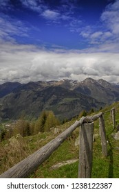 Fence on Malga Stain in Front of a beautyful Panorama with Mountains, clouds an a blue sky