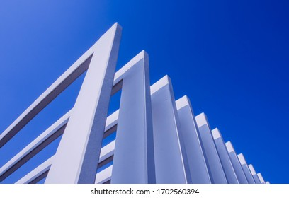 The fence on the sky background against the wall And abstract architecture contrasting with the blue sky With clear and beautiful light shadows Modern concepts