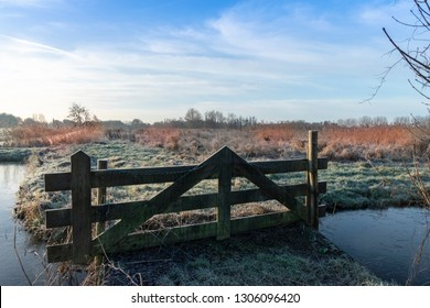Fence in a pasture with frozen grass in the winter. Blue sky.