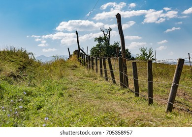 fence, path, and clouds meeting behind a green hill in nature
