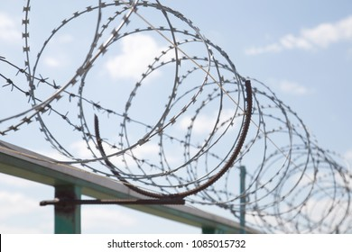 Fence with razor barbed wire protection against blue sky background. Dictatorship and tyranny concept
