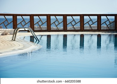 Fence of the resort pool reflected on the water. Pure blue sky, sea and mountains  on the background.