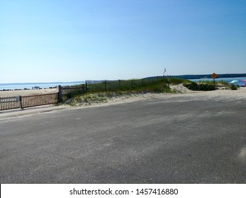 A fence separating the beach from the parking lot in New Suffolk, New York