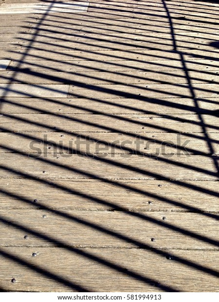 Fence shadows on wooden platform.